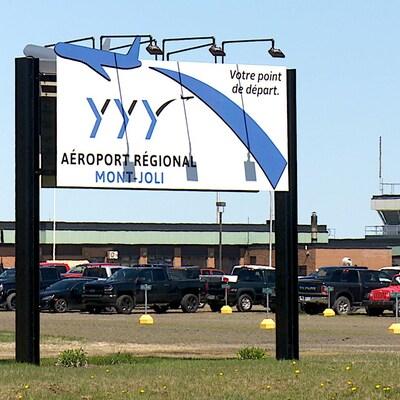 L'affiche de l'aéroport et des bâtiments derrrière.
