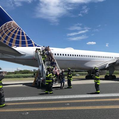 Le personnel d'urgence aide les passagers à descendre d'un avion après une sortie de piste d'un appareil de United Airlines à l'aéroport international Newark Liberty le samedi 15 juin 2019 à Newark.