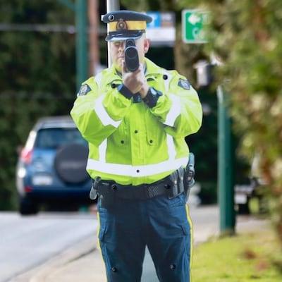 Un réplique en deux dimensions d'un policier pointant un radar est installée sur le coin d'une rue.