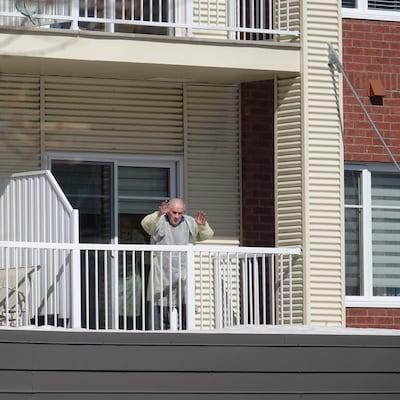 Une personne âgée, habillée d'une jaquette d'hôpital, salue depuis son balcon.