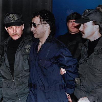 Allan Legere vêtu d'une tunique bleue, fraîchement rasé et portant des verres fumés, est menotté et escorté par des policiers.