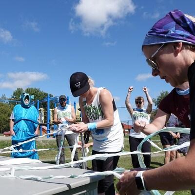 Trois personnes font des tresses avec de longs rubans de plastique attachés à une table.