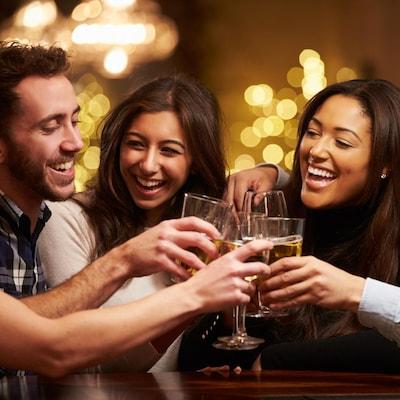 Cinq jeunes adultes trinquent en souriant.