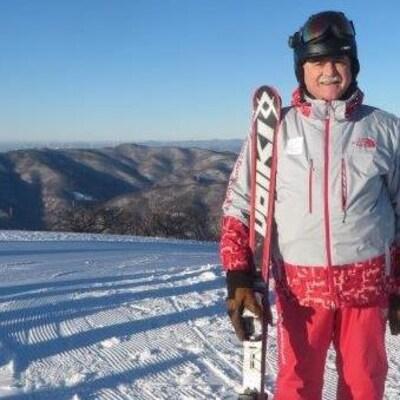 André Robert Labine tenant ses skis sur le haut d'une pente.