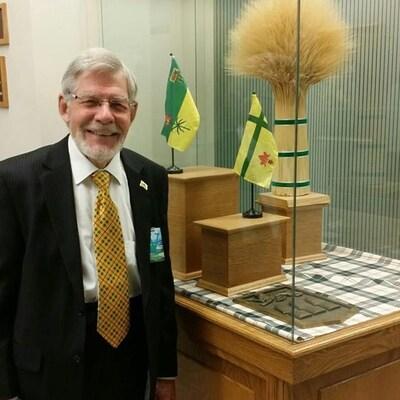 Anthony Drake devant deux drapeaux de la Saskatchewan.
