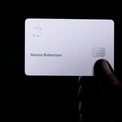 Une personne tient dans sa main gauche un iPhone où s'affiche l'application Apple Pay et dans sa main droite une carte de crédit Apple Card.