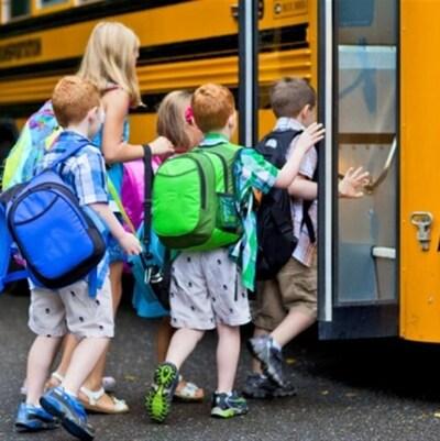 Des enfants montent à bord d'un autobus scolaire.