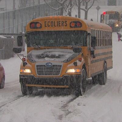 Un autobus scolaire sur une route enneigée.
