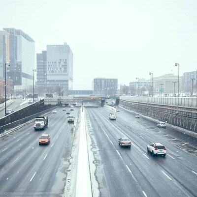 Des voitures circulent sur l'autoroute alors qu'il tombe sur la ville de gros flocons de neige.