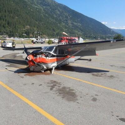 Le petit avion à hélice se trouve au milieu d'un stationnement avec une montagne au loin.