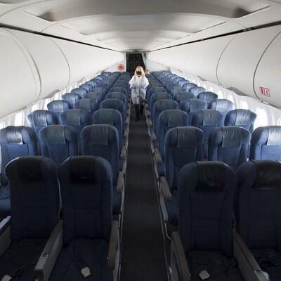 Une femme marche dans l'allée centrale d'un avion d'Air Canada. Elle porte un masque, un sarrau blanc et des gants.
