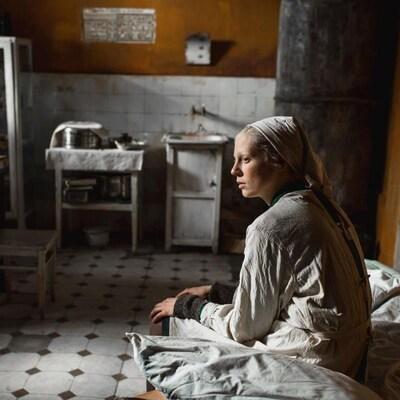 Une femme portant un foulard sur la tête est assise sur un lit dans une pièce à l'allure défraîchie.