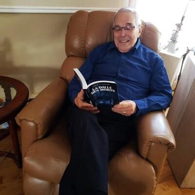 Benoît Bouchard lit un livre assis dans un fauteuil.