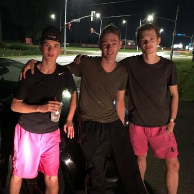 Trois adolescents adossés contre une voiture, tard la nuit.