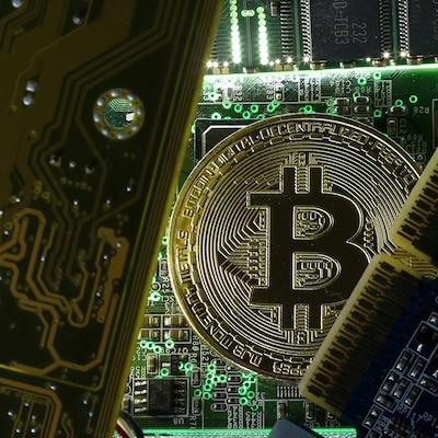 Une pièce de monnaie bitcoin parmi des cartes informatiques.