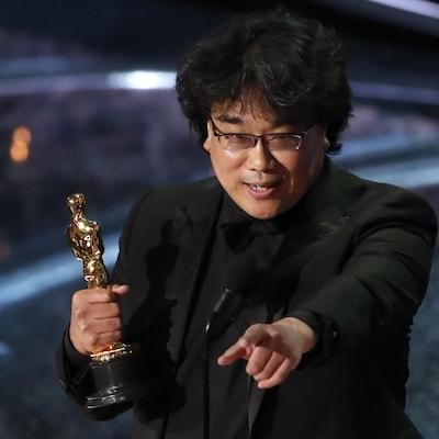 Un homme sur scène tient l'Oscar dans sa main droite et pointe la salle de sa main gauche.