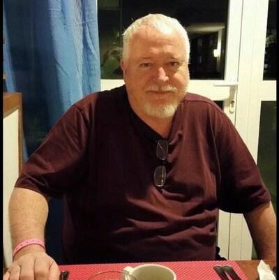 Photo de Bruce McArthur à table portant un t-shirt brun.