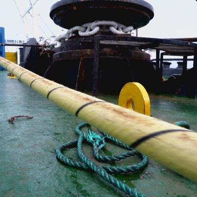 On voit le câble sur le pont du navire qui est en train d'être déroulé.