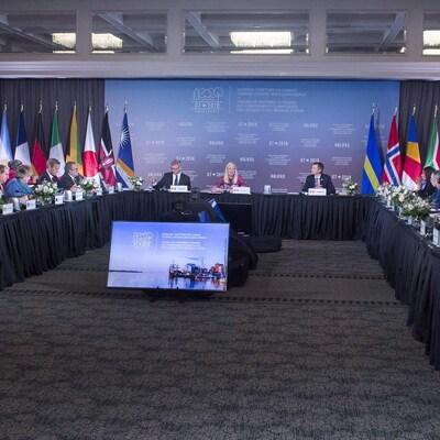 Une photo d'une rencontre présidée par la ministre de l'Environnement du Canada. Sur le long de deux tables, des représentants de plusieurs pays écoutent. Des drapeaux de plusieurs pays sont suspendus.