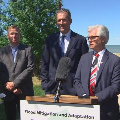 Plusieurs hommes en costume se tiennent devant un micro devant un lac.