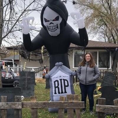 Carol Cassell se tient fièrement parmi des décorations d'Halloween installées sur le terrain avant de sa maison