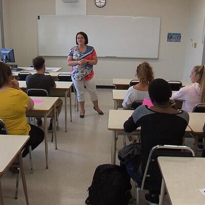 La professeure est debout au milieu de la rangée de bureaux et enseigne à une dizaine d'étudiants.