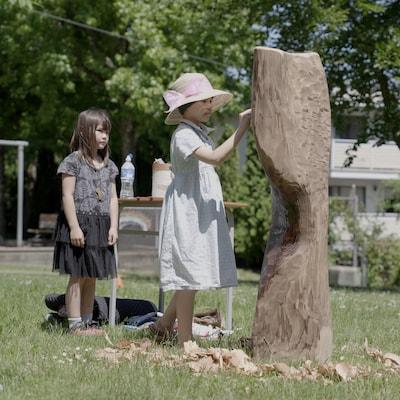 Une jeune enfant touche une sculpture.