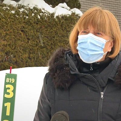 Une personne qui porte un masque parle au micro devant sa maison.