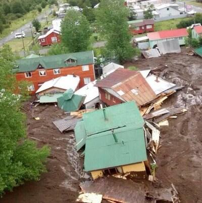 Des maisons sont englouties jusqu'au toit par une énorme coulée de boue.