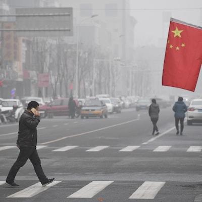 Un Chinois marche dans la rue.