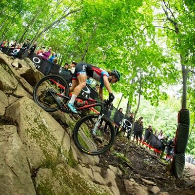 Cindy Montambault dévale une pente en vélo de montagne en forêt.