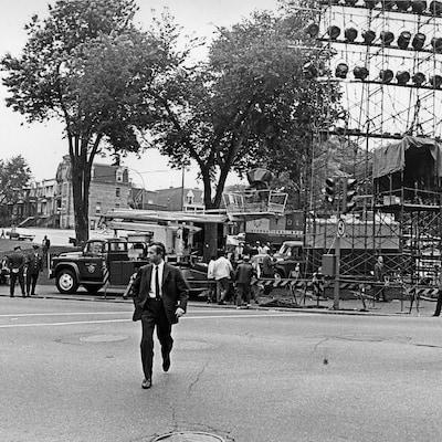 Claude Jean Devirieux, marchant devant les installations de Radio-Canada en prévision du défilé, dont une tour d'éclairage, un car de reportage et plusieurs barrières de sécurité.