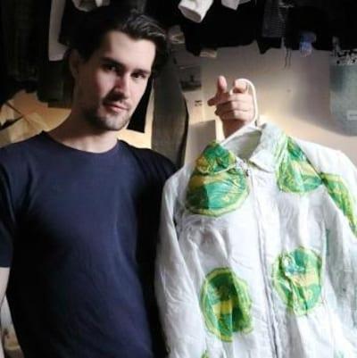 Un jeune homme tient une veste avec un cintre.