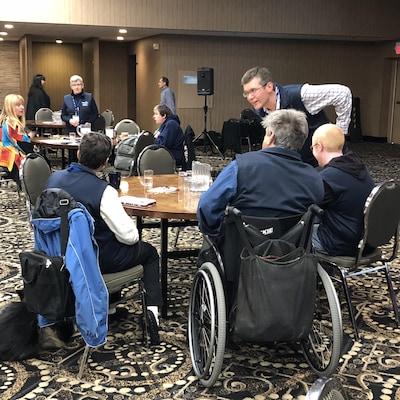 Des personnes assises autour de tables rondes dans pour assister à une présentation. Une des personnes est dans un fauteuil roulant.