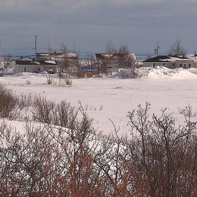 Au bout d'un champ enneigé, quelques maisons sont alignées.
