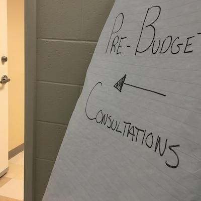 Une affiche indiquant une consultation prébudgétaire devant une porte entrouverte.