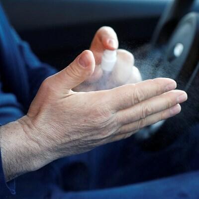 Un chauffeur de taxi se nettoie les mains avec du liquide désinfectant.