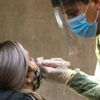 Un homme fait un prélèvement sur une femme dans le cadre d'un test de dépistage de la COVID-19.