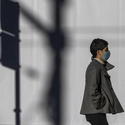 Une personne masquée marche dans le centre-ville de Vancouver.