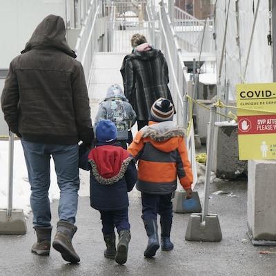 Une homme et deux enfants se rendent dans une clinique de dépistage de Montréal.