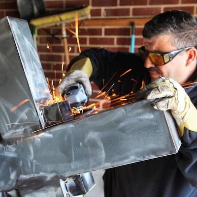 Un homme travaille une croix en métal.