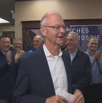 Ches Crosbie souriant, entouré de ses partisans qui applaudissent.