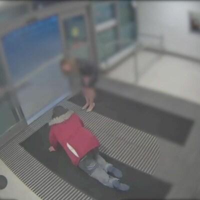 Une homme portant un manteau rouge marche à quatre pattes vers une sortie. Une femme se tient près de lui.