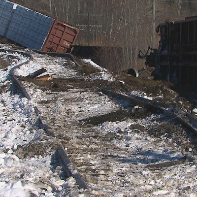 Deux wagons sont détachés l'un de l'autre et sont renversés sur le côté. Les rails sont arrachés et ont dévié de leur trajectoire.