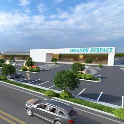 Le dessin d'architecte montre des magasins grande surface entourés de places de stationnement, le long d'une rue.