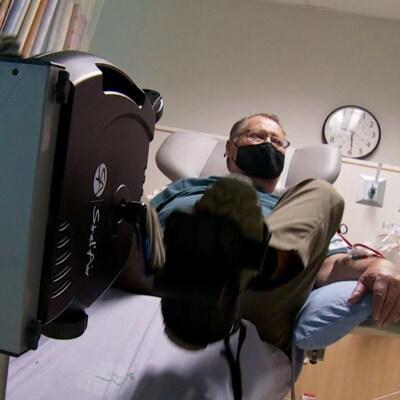 L'homme pédale tout étant assis dans un fauteuil durant son traitement de dialyse.