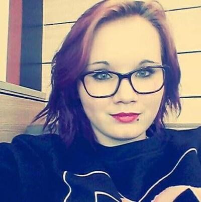 Un auto-portrait d'une jeune femme avec un piercing à la lèvre inférieure.