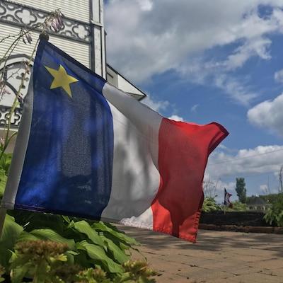 Un drapeau rouge, blanc et bleu avec une étoile jaune dans le coin gauche, planté dans une platebande de verdure devant un église blanche en bois.