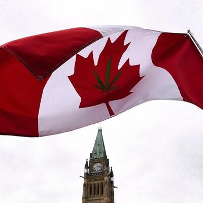 Un drapeau du Canada, où a été brodé une feuille de cannabis, flotte devant la colline du Parlement à Ottawa.