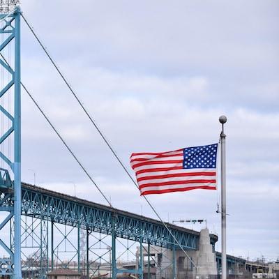 Les drapeaux du Canada et des États-Unis flottent devant le pont Ambassadeur.